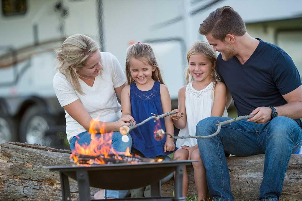 Family roasting marshmallows around a fire